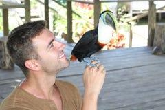 Homme et son oiseau domestiqué de toucan photo stock