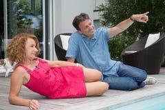 Homme et woma à la piscine à la maison, homme dirigeant quelque chose Photos libres de droits