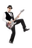 Homme euphorique jouant une guitare basse Images stock