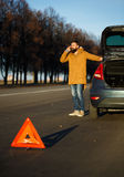 Homme examinant les voitures endommagées d'automobile après interruption Photos stock
