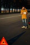Homme examinant les voitures endommagées d'automobile après interruption Photographie stock libre de droits