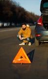 Homme examinant les voitures endommagées d'automobile après interruption Photos libres de droits