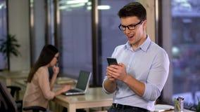 Homme excit? utilisant l'application de smartphone dans le bureau, technologie moderne, instrument images libres de droits