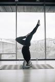 Homme expérimenté de yoga faisant de diverses poses à l'intérieur, vue panoramique de ville au fond Image stock