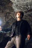 Homme explorant la caverne énorme Les voyageurs d'aventure ont habillé le chapeau de cowboy et le sac à dos, veste en cuir itinér image libre de droits