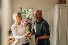 Homme exprimant son amour pour son épouse lui donnant un groupe de fleurs à la maison Femme supérieure heureuse de voir son mari  image libre de droits