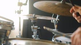 Homme extrême de plan rapproché dans des vêtements noirs jouant sur des tambours et des tambour-plats dans le studio clips vidéos