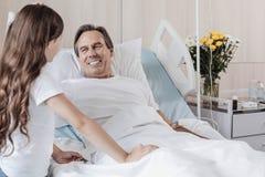 Homme extrêmement heureux souriant tout en regardant la fille dans l'hôpital image libre de droits