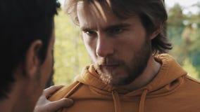 Homme fâché aux cheveux longs discutant avec l'ami dans la forêt banque de vidéos