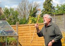 Homme fâché avec un bâton de marche Images libres de droits