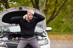 Homme fâché avec une voiture cassée photo stock