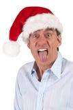 Homme fâché dans le chapeau de Santa collant à l'extérieur la langue Image stock