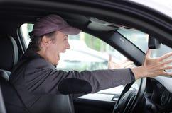 Homme fâché de renversement à la roue conduisant sa voiture criant Images stock