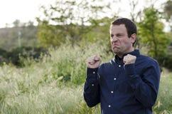 Homme fâché dehors avec les poings serrés Photos stock