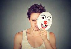 Homme fâché frustrant se cachant derrière le visage heureux Image stock