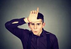 Homme fâché montrant le signe de perdant regardant avec dégoût l'appareil-photo Image stock