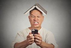 Homme fâché soumis à une contrainte poussant à son téléphone intelligent Photos stock