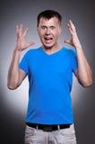 Homme fâché sur le fond gris Photographie stock libre de droits