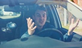 Homme f?ch? conduisant un v?hicule discutant et faisant des gestes serrant sa main perplexe Massage facial négatif de type irrité images stock