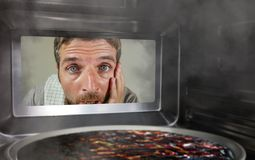 Homme factice malpropre et drôle dans la cuisine regardant par la micro-onde ou la pizza de four brûlant trop cuite faisant un dé photo stock