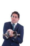 Homme faible avec l'expression dans le costume soulevant un poids Photo stock