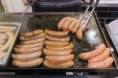 Homme faisant cuire des saucisses sur un gril plat Photos stock