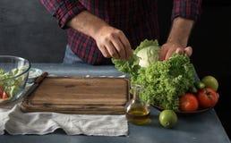 Homme faisant cuire la salade de légumes dans la cuisine à la maison Photos libres de droits