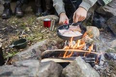 Homme faisant cuire la viande au-dessus du feu au terrain de camping images libres de droits