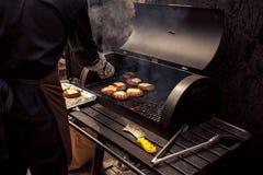 Homme faisant cuire la viande pour le cheeseburger sur le gril Images stock