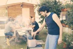 Homme faisant cuire la viande sur le barbecue Photos libres de droits