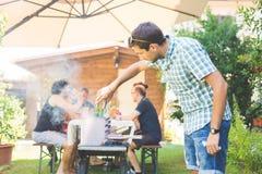 Homme faisant cuire la viande sur le barbecue Images stock
