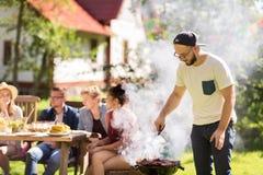 Homme faisant cuire la viande sur le gril de barbecue à la partie d'été Photographie stock