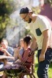 Homme faisant cuire la viande sur le gril de barbecue à la partie d'été Photographie stock libre de droits