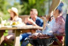 Homme faisant cuire la viande sur le gril de barbecue à la partie d'été Photo stock