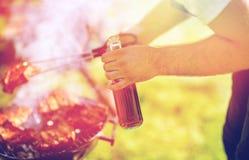 Homme faisant cuire la viande sur le gril de barbecue à la partie d'été Images stock