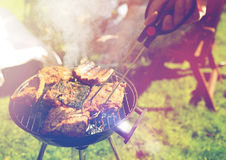 Homme faisant cuire la viande sur le gril de barbecue à la partie d'été Images libres de droits