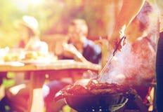 Homme faisant cuire la viande sur le gril de barbecue à la partie d'été Photos stock