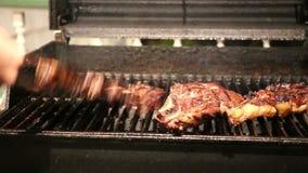 Homme faisant cuire le gril de déchirure de porc de barbecue sur le charbon de bois banque de vidéos
