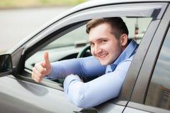 Homme faisant des pouces dans la voiture Photographie stock