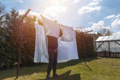 Homme faisant des travaux du m?nage et accrochant la blanchisserie photos libres de droits
