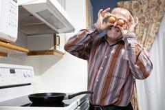 Homme faisant frire des oeufs Images libres de droits
