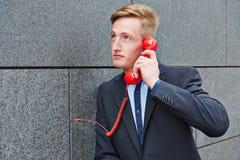 Homme faisant l'appel avec le téléphone rouge sur le mur photo libre de droits