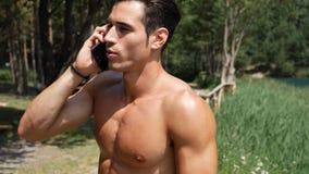 Homme faisant l'appel téléphonique au lac photographie stock libre de droits