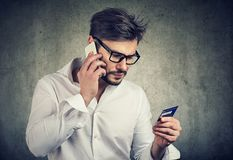 Homme faisant l'appel tenant la carte de crédit Photos stock