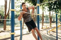 Homme faisant l'exercice sur la barre horizontale extérieure photo libre de droits