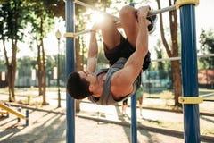 Homme faisant l'exercice sur la barre horizontale extérieure photographie stock