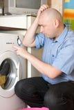 Homme faisant la blanchisserie à sa maison photographie stock libre de droits