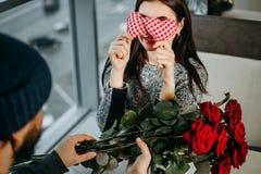 Homme faisant la surprise pour son amie donnant un bouquet de RO rouge Photo libre de droits