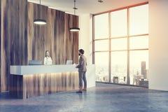 Homme faisant le coin de réception de lobby en bois et blanc de bureau Photo libre de droits