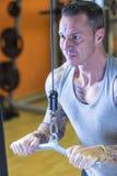 Homme faisant le refoulement de poulie - routine de séance d'entraînement photographie stock